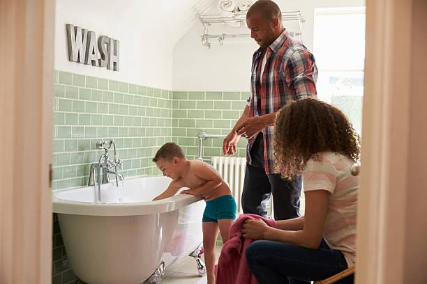 parents and son having fun at bath time together - kinderbadewanne stock-fotos und bilder