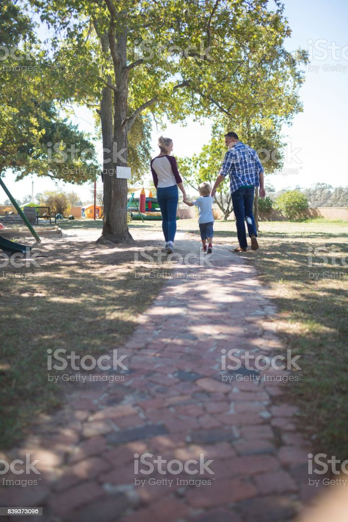 Parents and son holding hands while walking on footpath at park stock photo