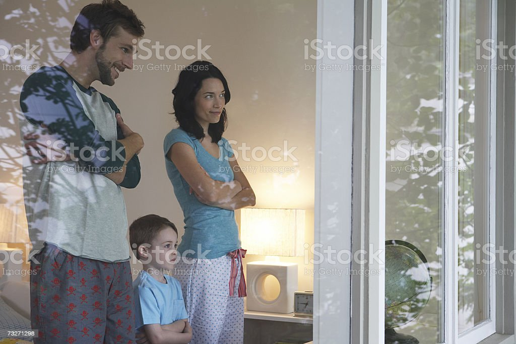 Parents and son (3-5) looking out through bedroom window royalty-free stock photo