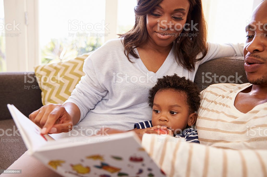 Parents And Son Reading Book On Sofa At Home Together stock photo