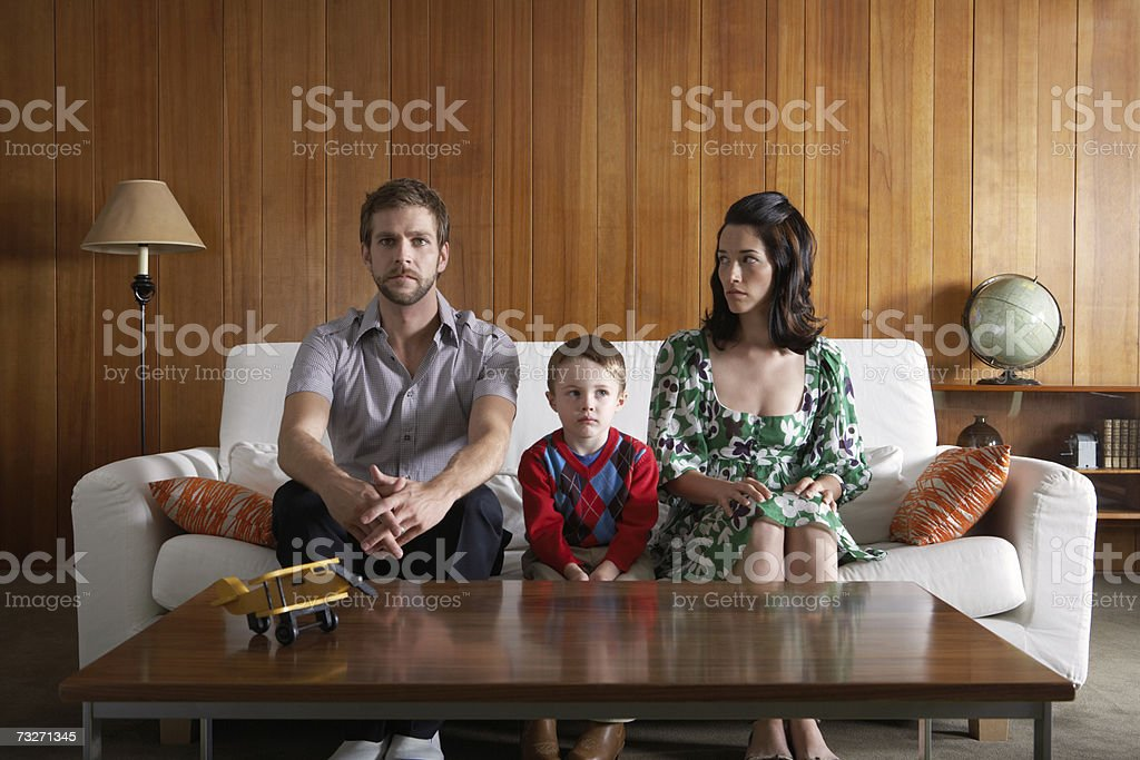 Parents and son (3-5) sitting on couch in living room stock photo