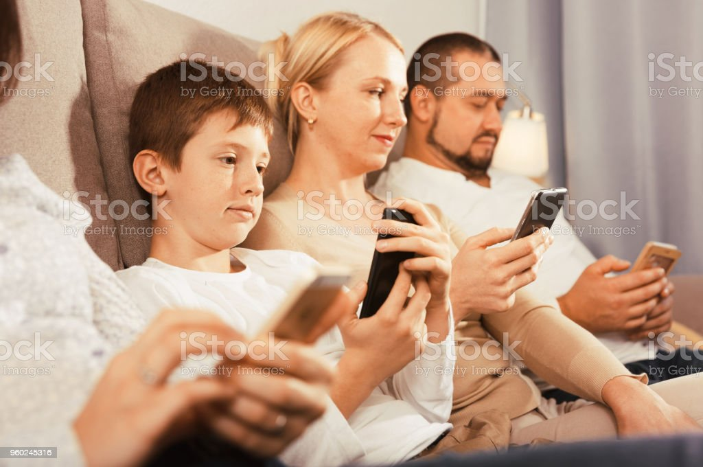 Parents and son using phones at home stock photo
