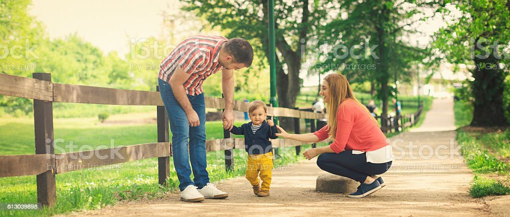 Parents and their baby boy learning to walk stock photo