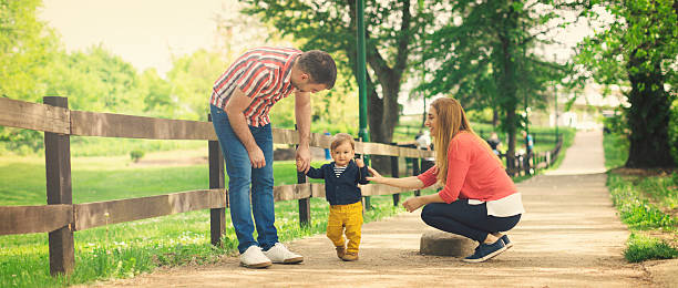 parents and their baby boy learning to walk - fall prevention stock photos and pictures