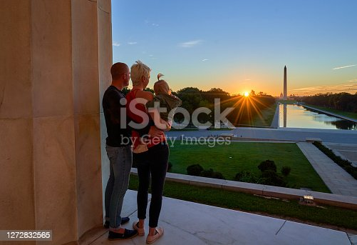 Couple and Their Toddler Daughter  at the Lincoln Memorial with the Washington Memorial in the Background at Sunrise in Washington DC Capital of the USA