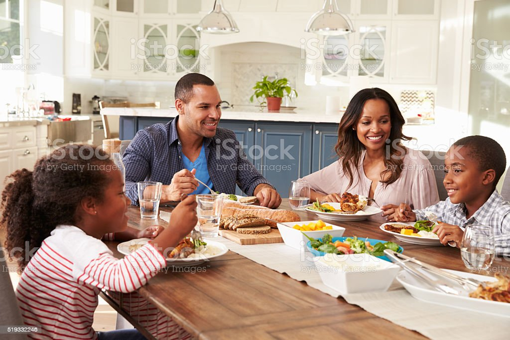 Parents and their two children eating at kitchen table stock photo