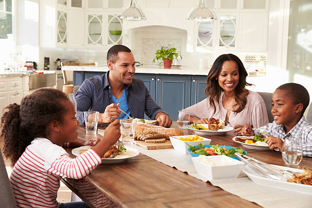 parents and their two children eating at kitchen table - dining table stock photos and pictures