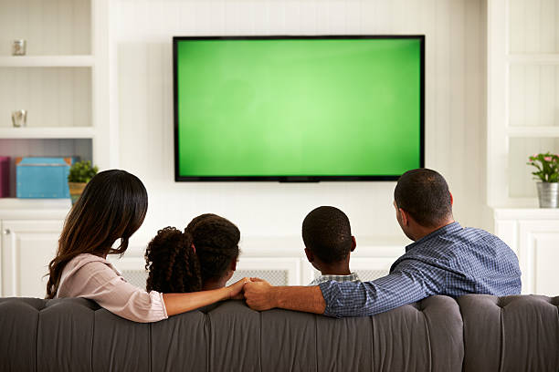 parents and their two children watching tv together at home - family watching tv stock photos and pictures