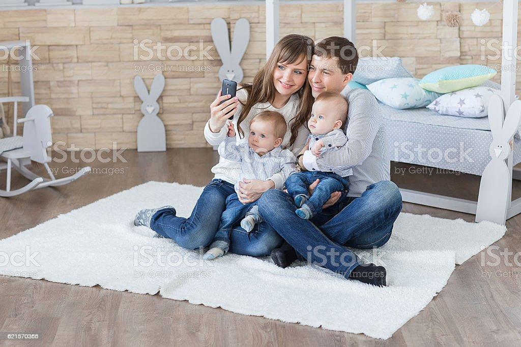 parents and  twins taking selfie by smartphone photo libre de droits