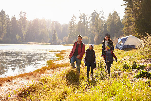 parents and two children on camping trip walking near - camping stock photos and pictures