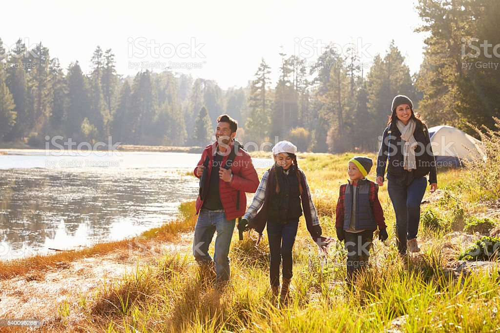 Parents and two children walking near a lake, close up stock photo