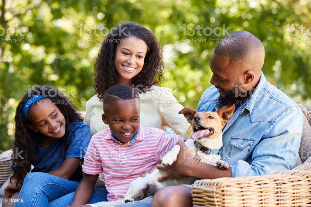 Parents and two kids sitting with pet dog in the garden stock photo
