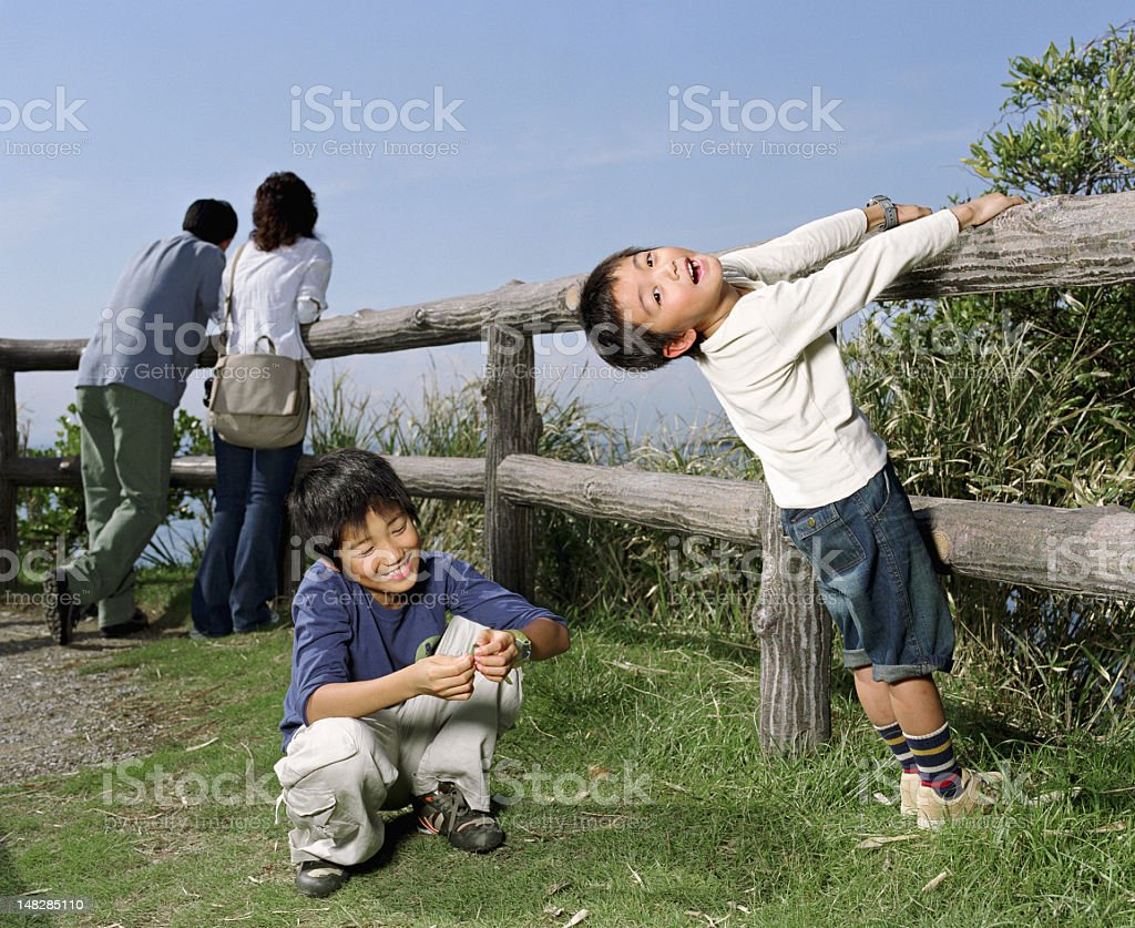 Parents and two sons (5-10) beside wooden fence (focus royalty-free stock photo