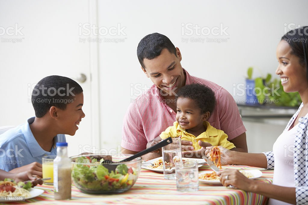 Parents and two young boys sharing a family meal together stock photo