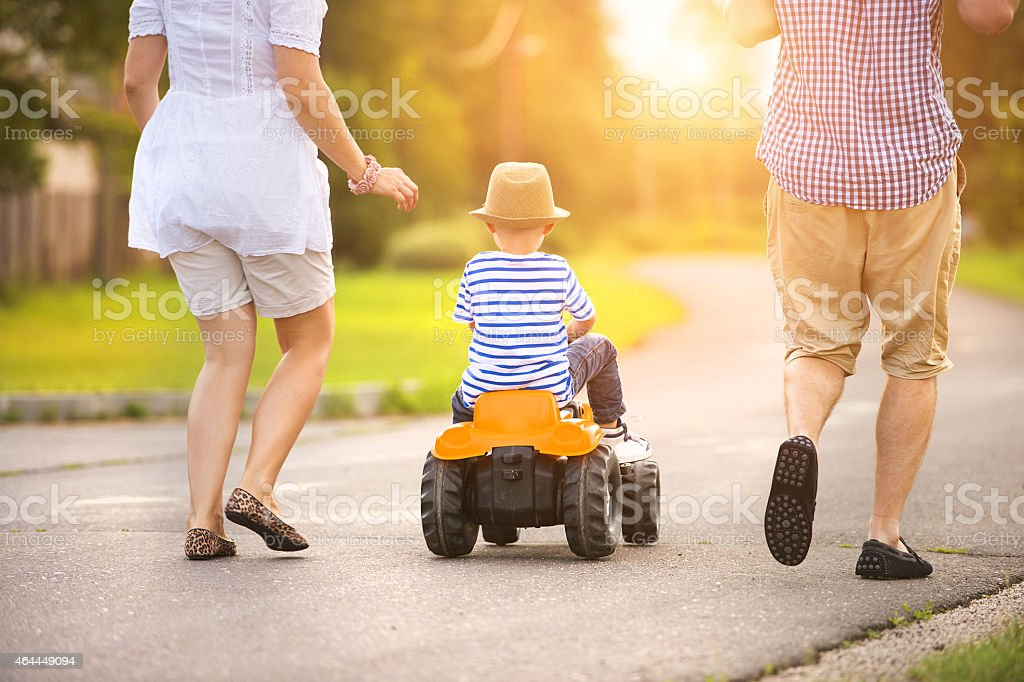Parents and with son on small car walking on street stock photo
