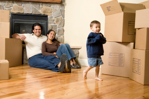 istock Parents and young child in an empty room with boxes, smiling 172965307