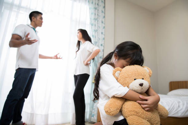 Parents are quarreling daughters feel stressed. She cried, hugging a teddy bear stock photo