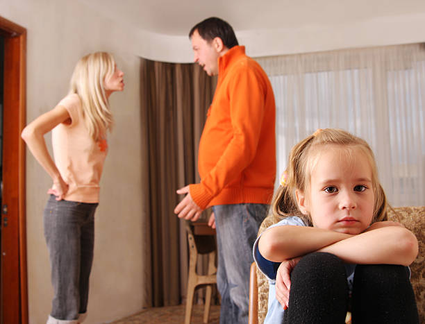 Parents arguing while child suffers stock photo