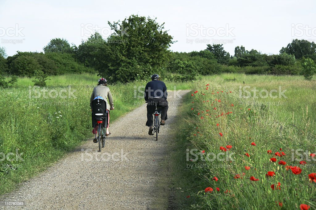 Parents biking in park with a child on the back. stock photo