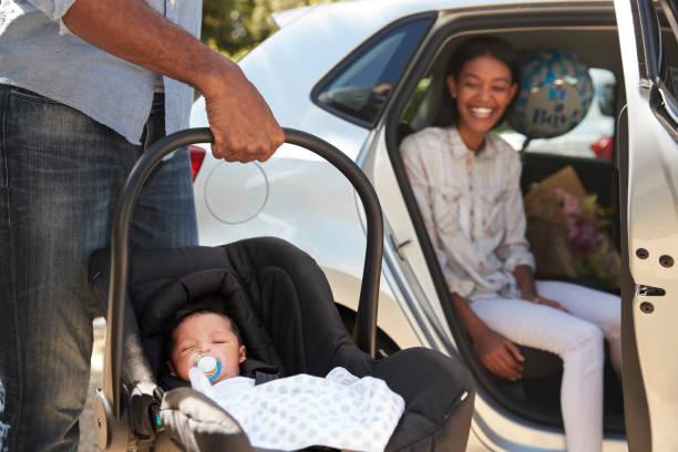 padres que recién nacido bebé casa en coche - llegada fotografías e imágenes de stock