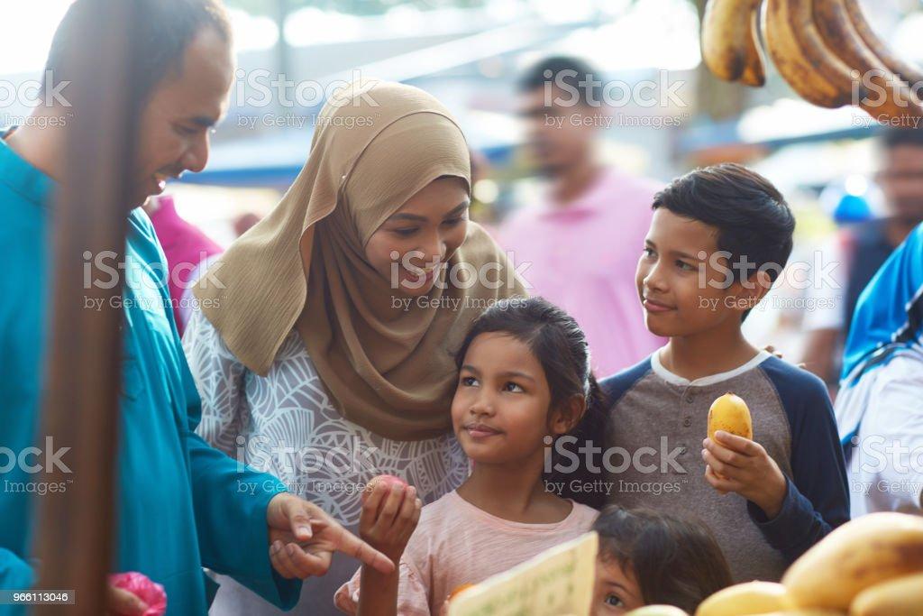 Föräldrar att köpa frukter med barn på marknaden - Royaltyfri 10-11 år Bildbanksbilder