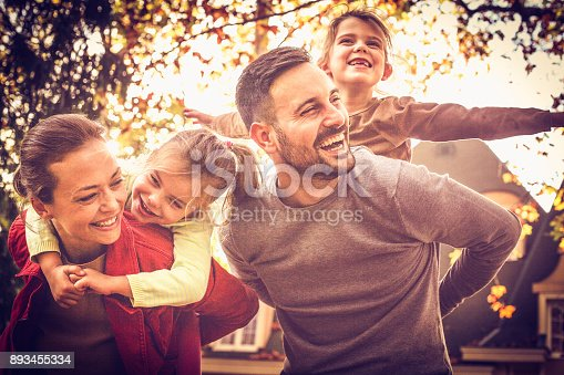 istock Parents carrying little girls on piggyback. Family time. 893455334