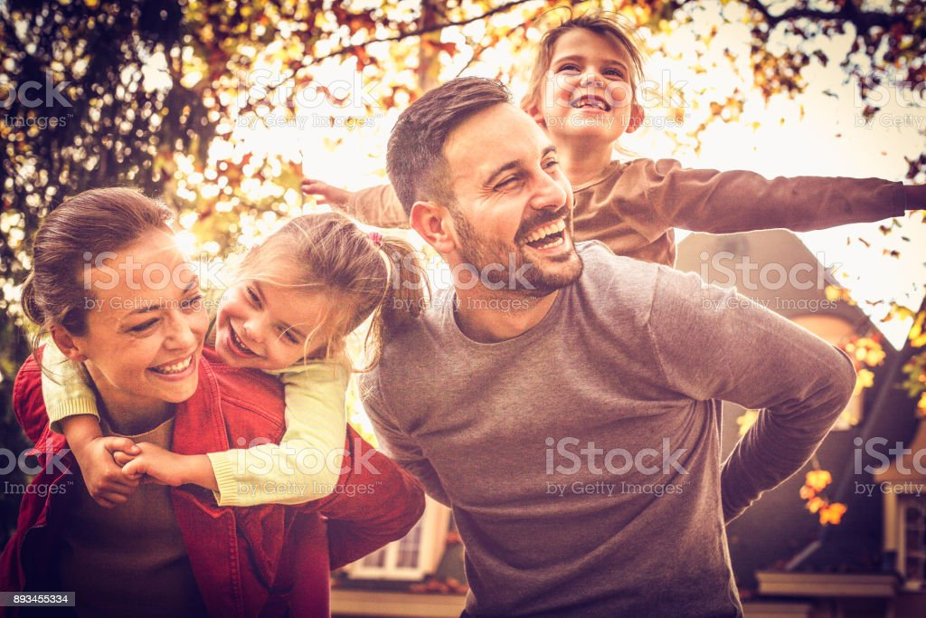 Parents carrying little girls on piggyback. Family time. - foto stock