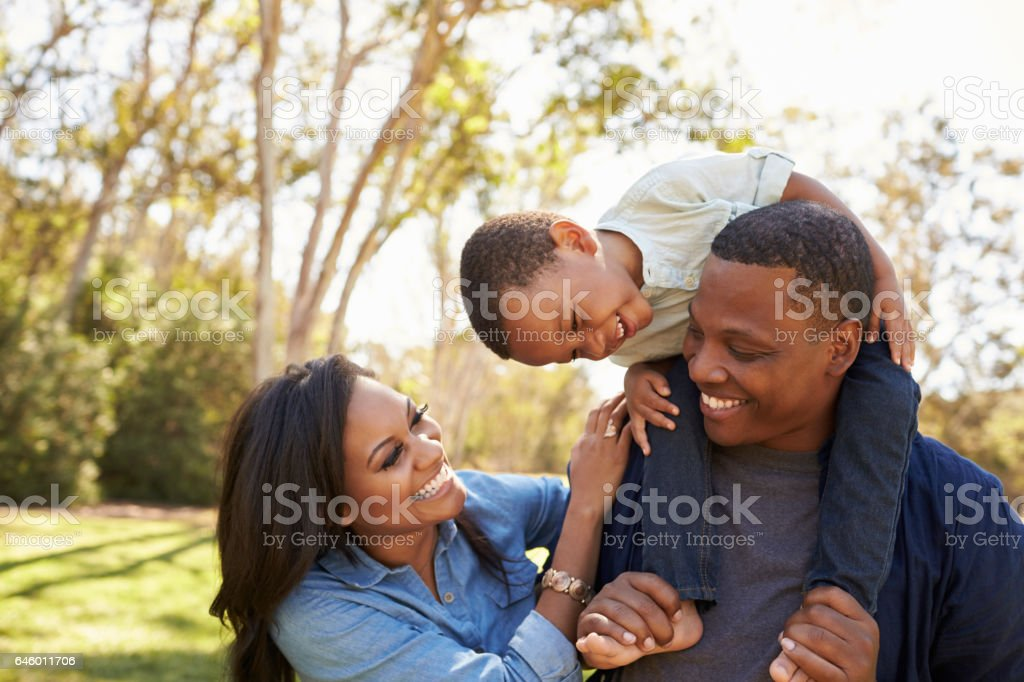 Parents Carrying Son On Shoulders As They Walk In Park stock photo