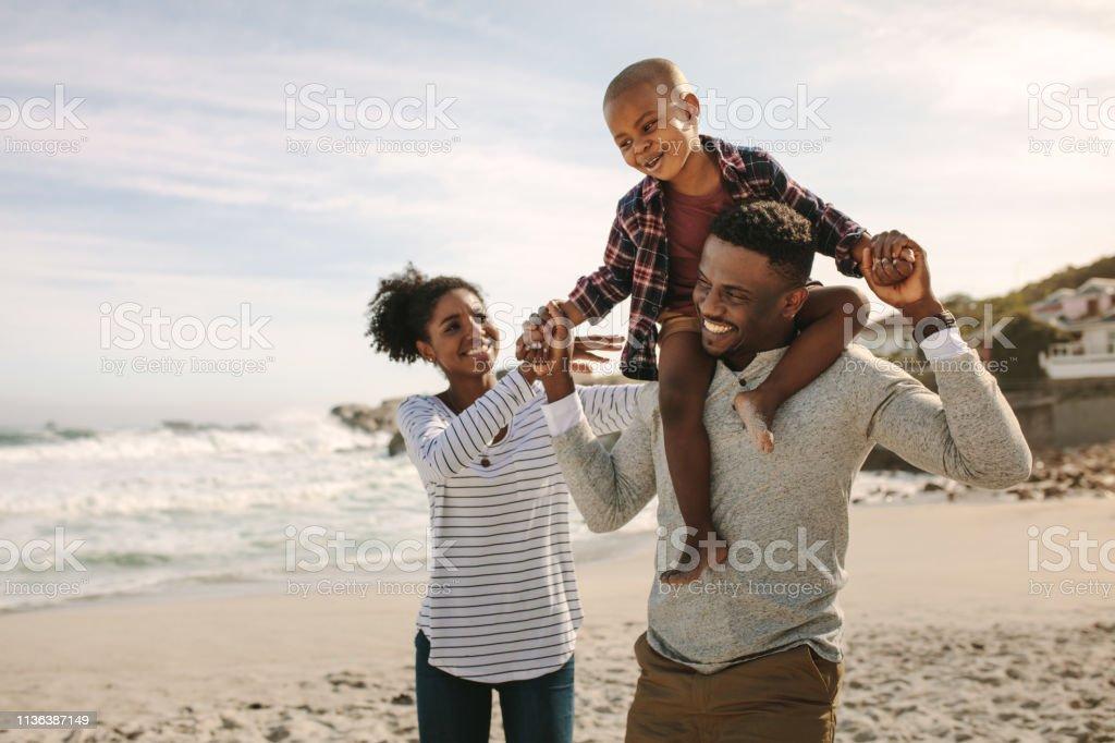 Plaj tatilinde omuzlarında oğlu taşıyan ebeveynler - Royalty-free Adamlar Stok görsel
