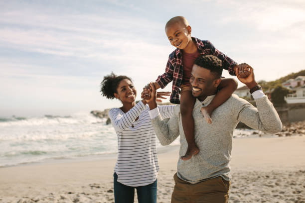 Parents carrying son on shoulders on beach vacation Parents carrying son on shoulders on beach vacation. African family of mother and father carrying son on his shoulders on vacation. african american ethnicity stock pictures, royalty-free photos & images