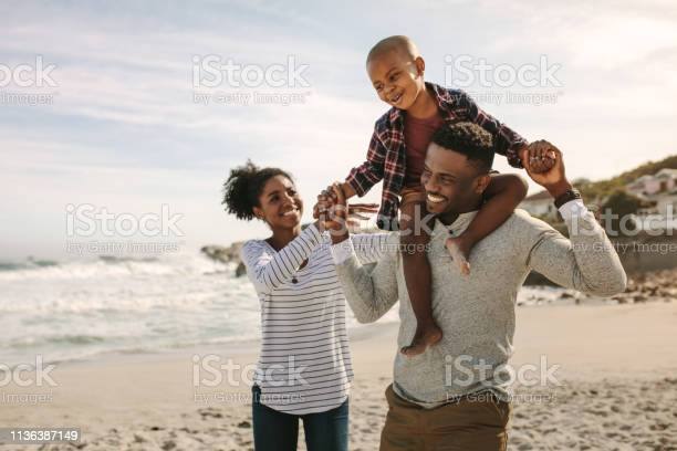 Parents Carrying Son On Shoulders On Beach Vacation Stock Photo - Download Image Now