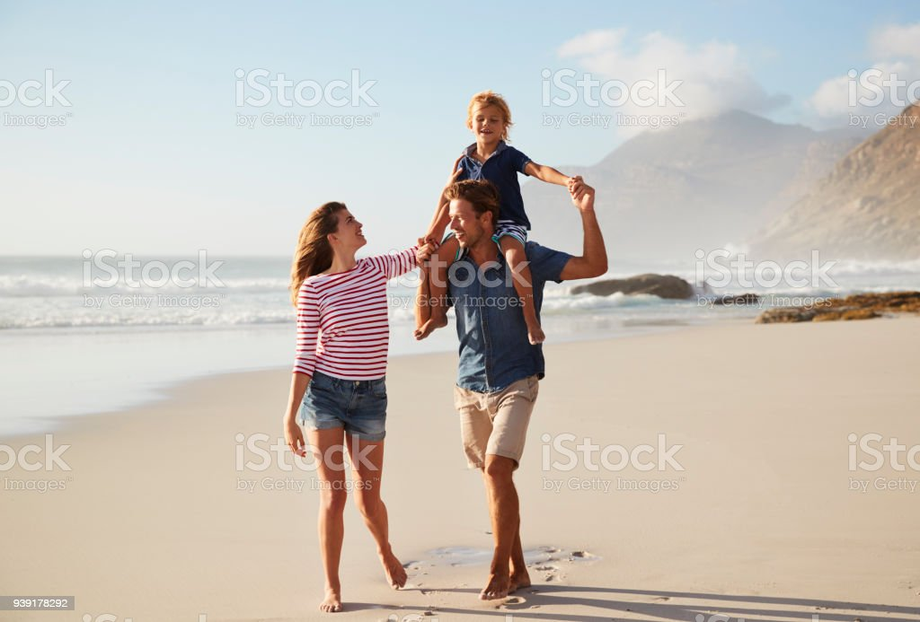 Parents Carrying Son On Shoulders On Beach Vacation royalty-free stock photo