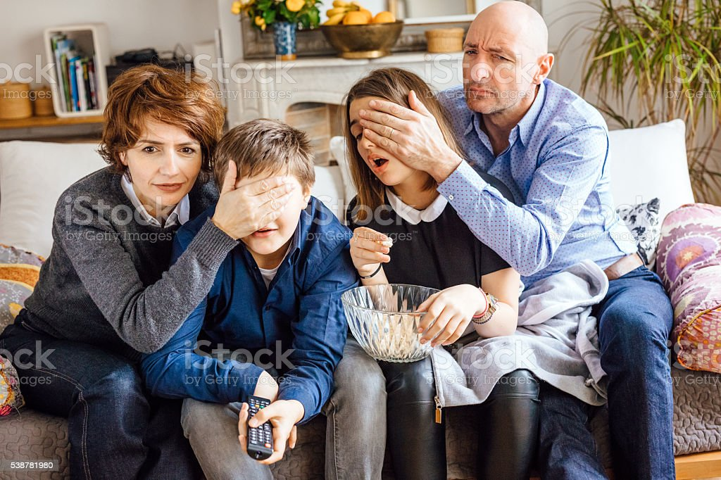 Parents cover their children's eyes and watching TV royalty-free stock photo