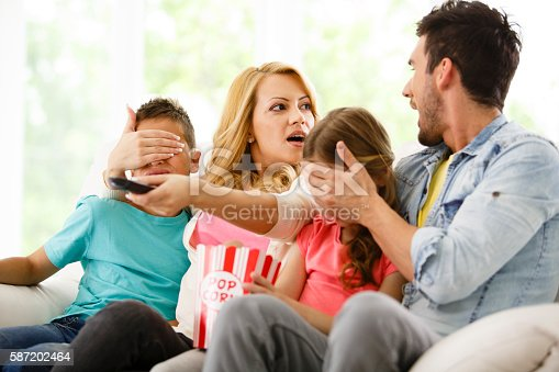 istock Parents cover their children's eyes while watching TV 587202464