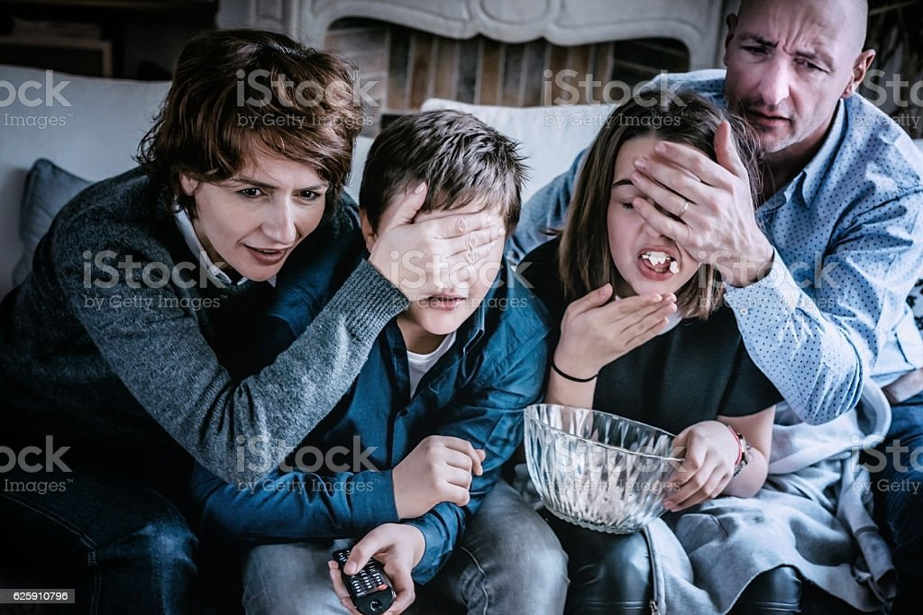 parents covering kids eyes for not watching adult tv content stock photo