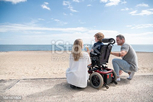 Mid adult mother and mature father kneeling by 6 year old child with muscular dystrophy by the beach, enjoying an ice cream while looking at the view. Clacton on Sea.
