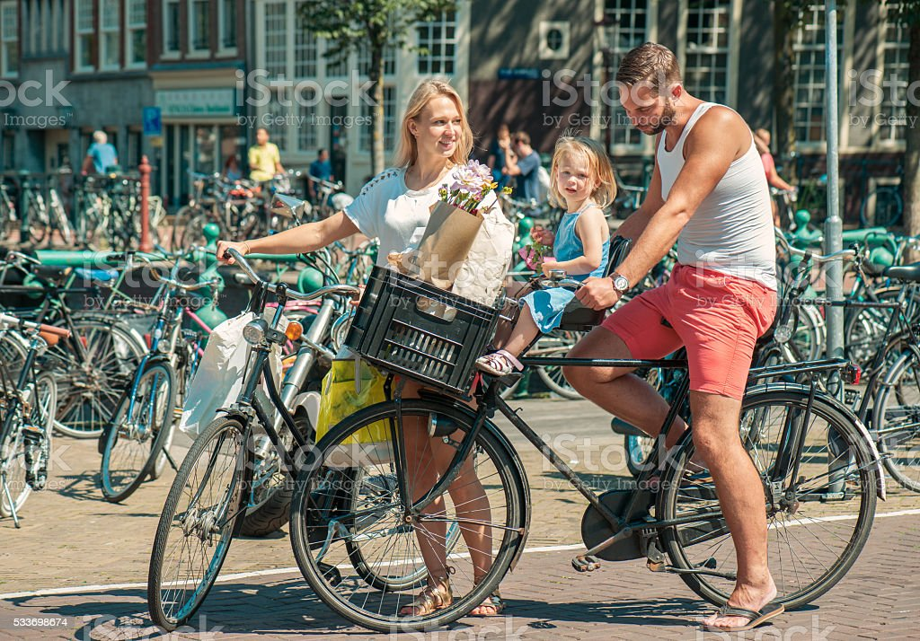 Parents cycling at the streets of Amsterdam stock photo