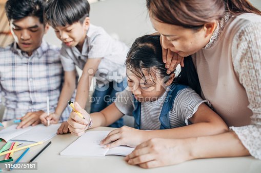 istock Parents doing homework with children at home 1150075161
