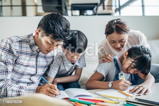 istock Parents doing homework with daughter and son at home 1150075229
