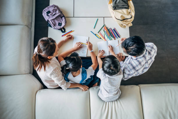 Parents doing homework with daughter and son at home Group of people, parents doing homework with two children together at home. homework stock pictures, royalty-free photos & images