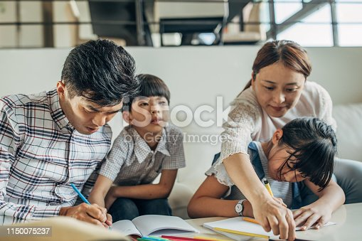 istock Parents doing homework with daughter and son 1150075237