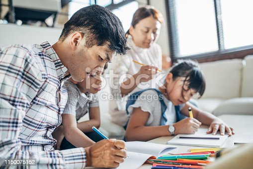 istock Parents doing homework with kids at home 1150075152