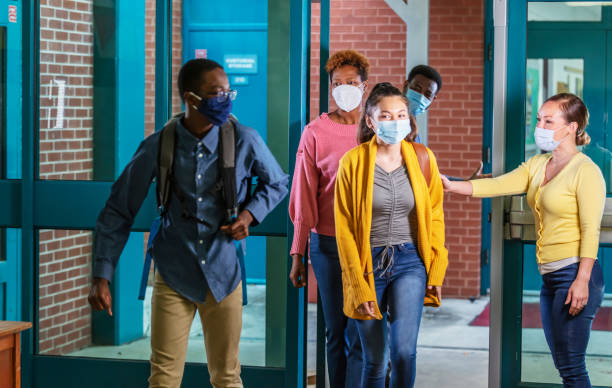 Parents drop middle school students off, with face masks stock photo