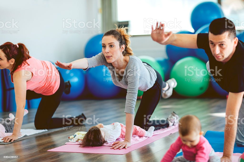 Parents Exercising with Their Babies in a Gym stock photo