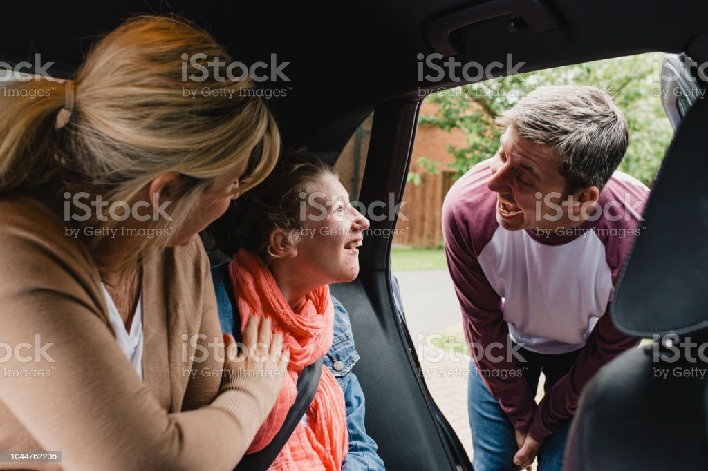Parents Getting Disabled Daughter in the Car stock photo