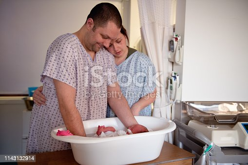 Parents gives a bath wrapped to their premature babyat hospital.  Color and horizontal photo was taken in Quebec Canada.