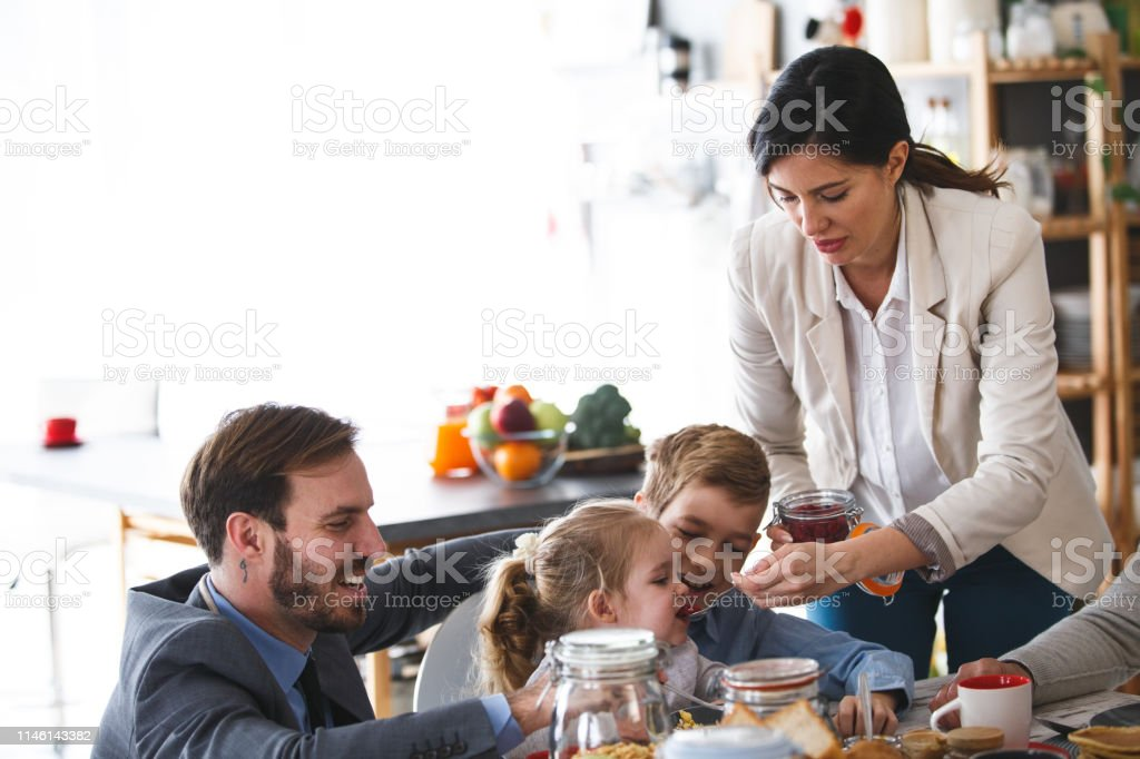 Mother and father are having breakfast with their son and daughter...