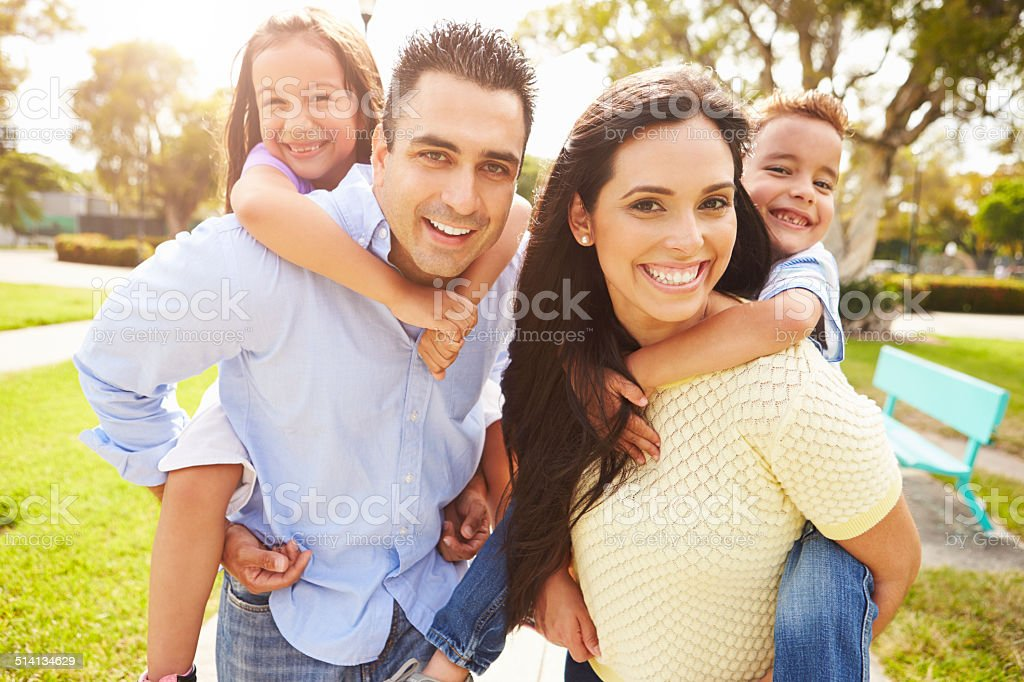 Padres dando Children Piggyback Ride In Garden - foto de stock