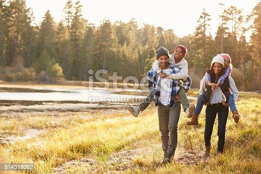 istock Parents Giving Children Piggyback Ride On Walk By Lake 514318052