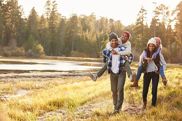 padres dando niños de lengüeta paseo a pie al lago - excursionismo fotografías e imágenes de stock